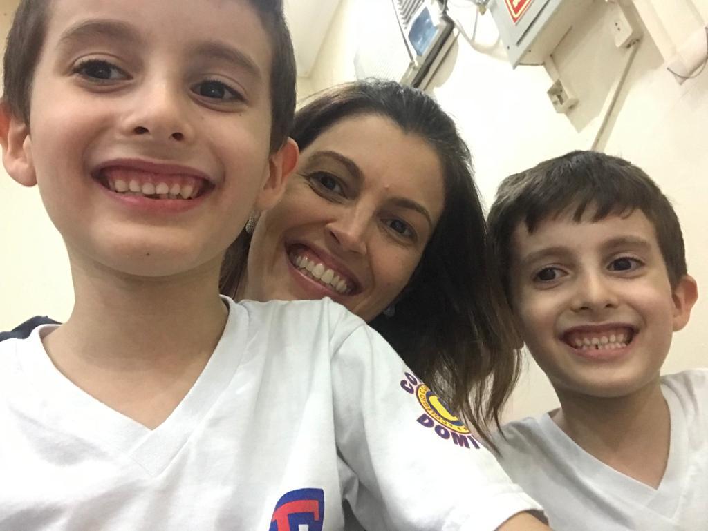 Os gêmeos autistas Pietro e Lorenzo posam sorrindo com sua mãe entre os dois