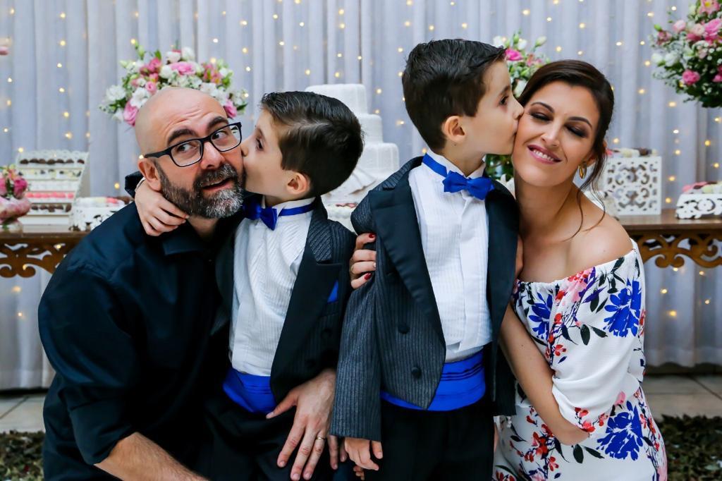 gêmeos autistas de 7 anos beijando o pai e a mãe