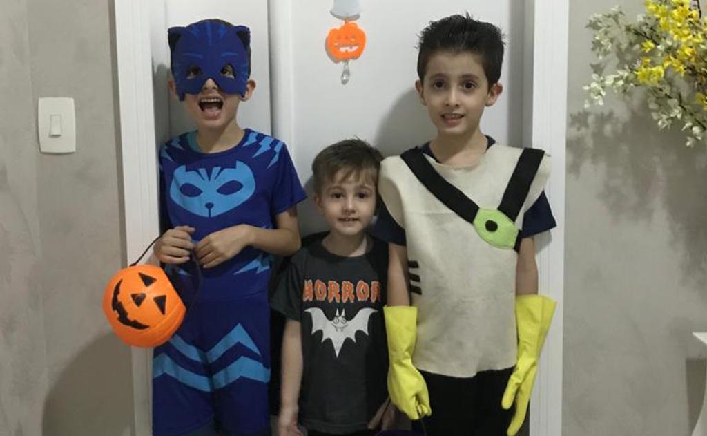 Os gêmeos autistas Pietro e Lorenzo com o irmão mais novo, vestidos com fantasias infantis