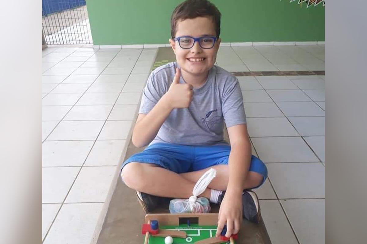 Nicolas, um pré-adolescente com transtorno autista posa para a câmera, sentado no chão, sorrindo e fazendo um joinha.