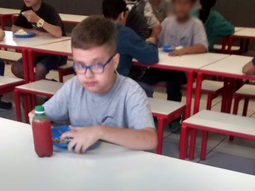 O menino Nicolas, que tem transtorno autista, está sentado sozinho numa mesa de refeitório escolar