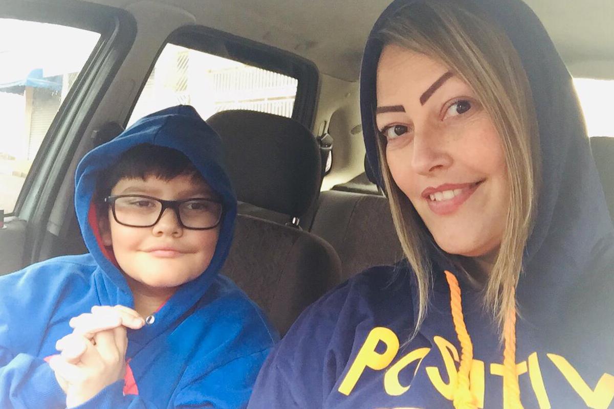 Marcela com seu filho autista Pedro, dentro de um carro